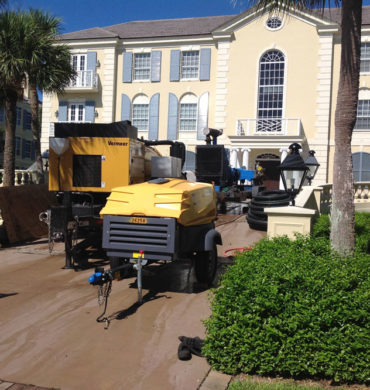 Set up in a driveway of a private residence: our vacuum recovery unit removing torchdown with our deck machine at 40,000 PSI.